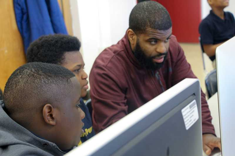 Candid photo of Co-founder Jerome Moore pairing with kids in after school coding program pilot, Ingenious Thought.